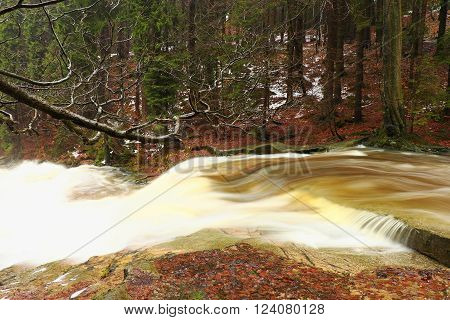 Winter at mountain river. Big stones in stream covered with fresh powder snow and lazy water with low level. Reflections of forest in water level.