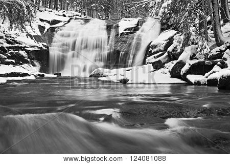 Winter view over snowy boulders to cascade of waterfall. Wavy water level.. Stream in deep freeze.