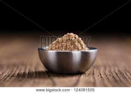 Portion of Galangal Powder(detailed close-up shot; selective focus) on wooden background