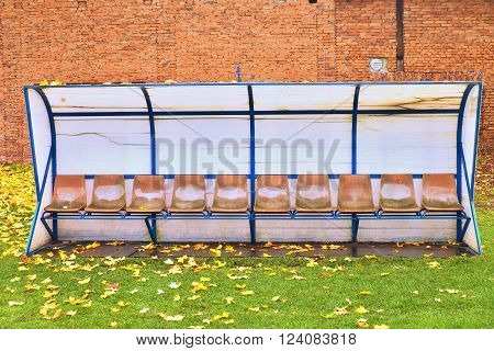 Old Plastic Seats On Outdoor Stadium Players Bench, Chairs With Worn Paint Below Yellow Roof.  Autum