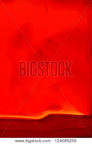 Abstract smudged red background with a dark red motion blur streak with gold trim at the bottom of the frame in vertical 3:2 format.