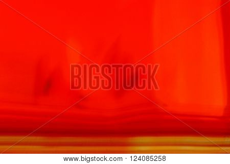 Abstract smudged red and orange blurred background with a gold set of motion blur streaks at the bottom of the frame in horizontal 3:2 format.