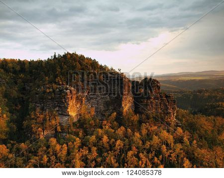 Autumn sunset view over sandstone rocks to fall colorful valley of Bohemian Switzerland.