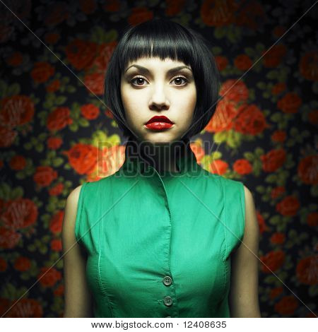 Beautiful lady-doll in green dress at flower background