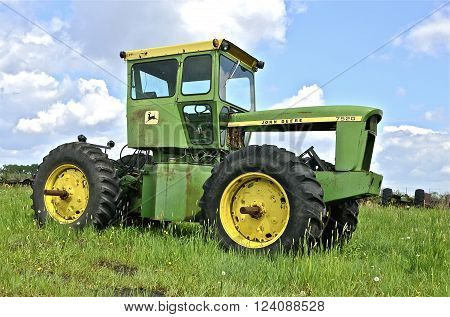 BARNESVILLE, MINNESOTA- June 2, 2014; An old four wheel drive John Deere is parked without an engine and is a product of John Deere Co, an American corporation that manufactures agricultural, construction, forestry machinery, diesel engines, and drivetrai