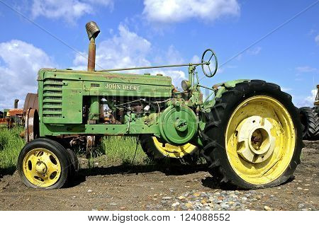 BARNESVILLE, MINNESOTA- June 2, 2014; An old two cylinder John Deere is parked with a flat tire and is a product of John Deere Co, an American corporation that manufactures agricultural, construction, forestry machinery, diesel engines, and drivetrains