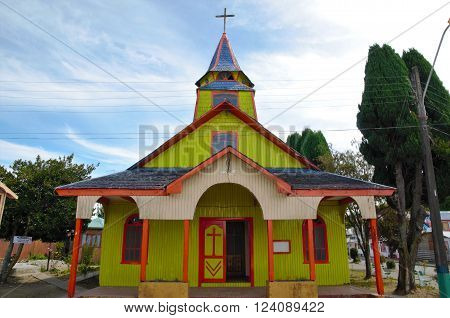 Long shot of the yellow and red wooden church in Quemchi on the island Chiloé in Chile