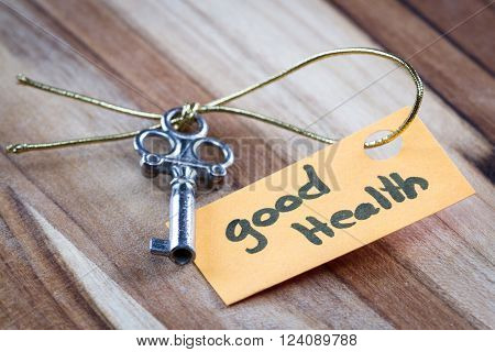 concept for a happy healthy life using an old decorative key and a hand written tag attached by a golden cord