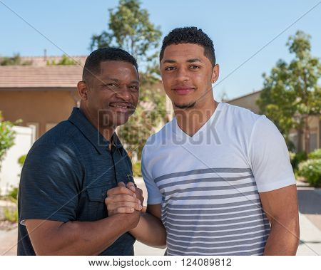 Multiracial father and teenage son posed with a handshake.