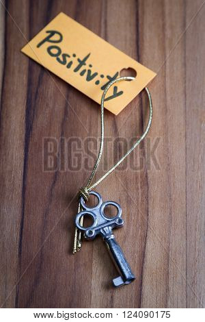 concept for a happy positive life using old decorative keys and a hand written tag attached by a golden cord