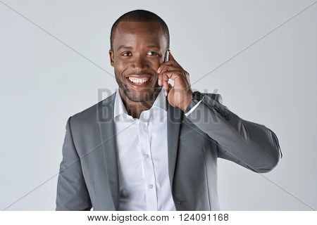 Black professional business man talking on his mobile cell phone having a conversation in studio