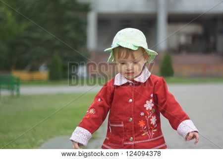 Beautiful little girl in the cap walking outdoors on the town square in the evening time