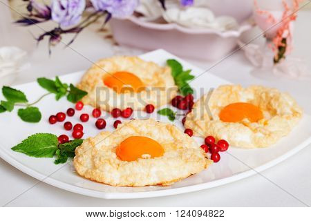 pastry with egg yolk, air biscuits, beaten egg white, berry, plate, still life