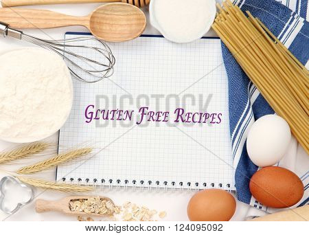 Basic baking ingredients and kitchen tools near note-book with text Gluten Free Recipes