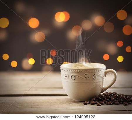 Cup of coffee with grains on brown background