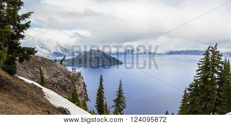 beautiful landscape with a mysterious fog creeping down into the Lake with snow still left on the rim