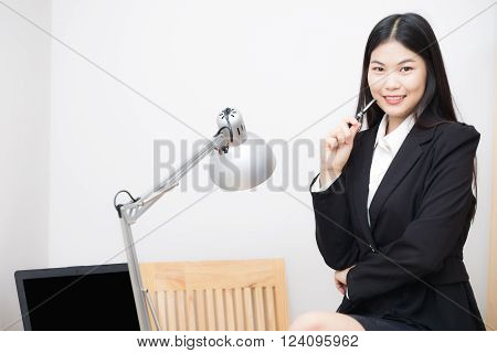 Asian business women sittting in white office with computer