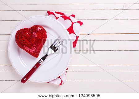 Romantic table setting. Decorative red heart knife and fork on white plate on white wooden background. Selective focus.