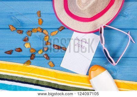 Amber stones in shape of sun and accessories for vacation and summer sunglasses sun lotion straw hat towel inscription summer 2016 on sheet of paper
