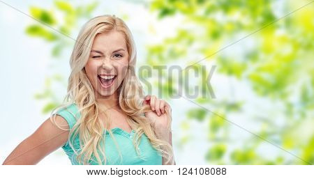 emotions, expressions, hairstyle and people concept - smiling young woman or teenage girl holding her strand of hair and winking over green natural background