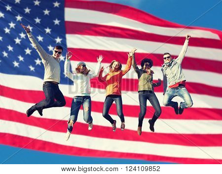 people, freedom, happiness and teenage concept - group of happy international friends in sunglasses jumping high over american flag background