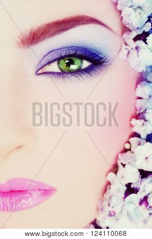 Vintage style close-up shot of beautiful woman with green eyes and bright makeup