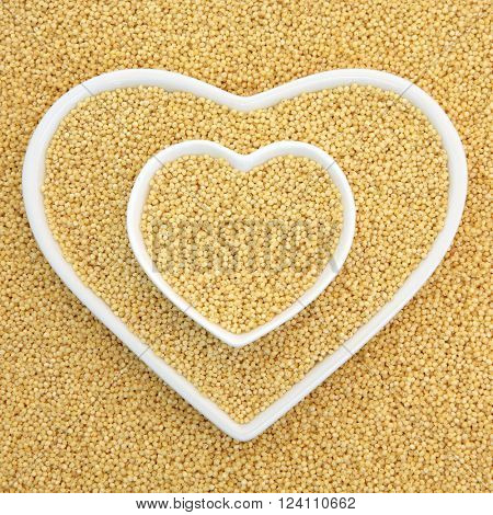 Millet grain super food in heart shaped bowls forming an abstract background.