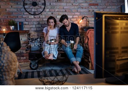 Young couple sitting at home on pallet furniture, watching tv, boring program.