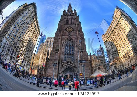 NEW YORK UNITED STATES - FEB 6 Colorful HDR image of New York's Trinity Church seen from Wall Street through fisheye lens. Trinity Church is a historic active parish church.. NYC USA Feb 6 2016