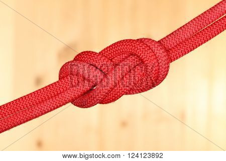 red double eght knot on wooden background