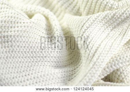 Fragment of a wrinkled knitted white piece of cloth fabric as a background texture