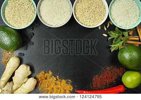 Four bowls with different types of rice: wild rice white basmati rice brown rice vegetables and indian spices on black background