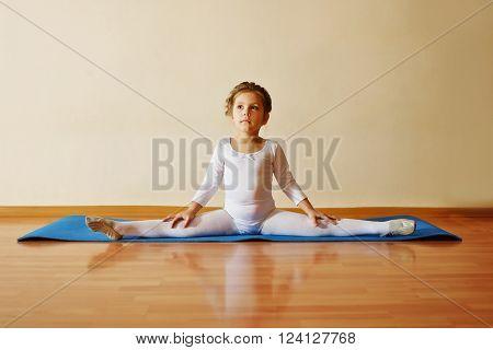 sweet toddler girl sitting in cross split