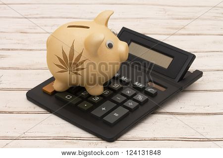 Profiting from selling marijuana, A golden piggy bank and calculator on a wood background with a marijuana leaf
