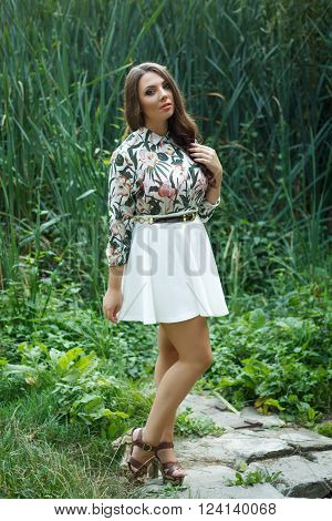 Beautiful brunette girl poses on green nature background outdoors