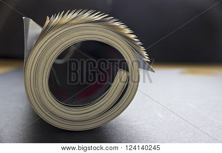 Rolled up magazine in table - close up