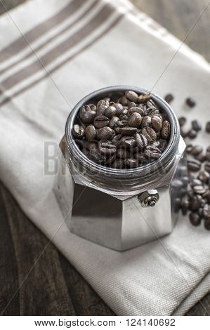 Italian coffee maker pot filled with coffee beans close up