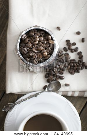 Italian coffee maker pot filled with coffee beans from above