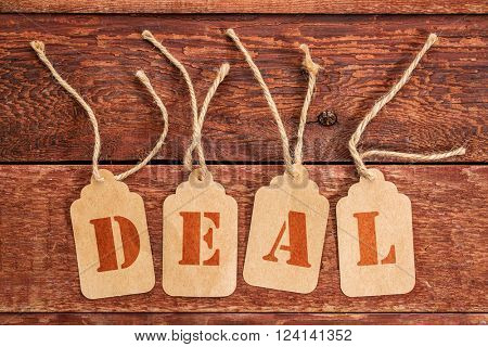 deal sign or concept - letters on  price tags against rustic red painted barn wood