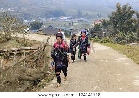 Sapa, Vietnam - February 16, 2016: Aboriginal people of the mountains of Sapa in north Vietnam dressed with their traditional attire and walking in their village.