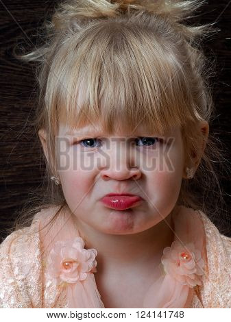 Offended child. Portrait of a little girl in a pink beautiful dress. The child is naughty