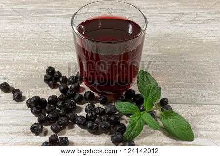 Aronia Berry Juice and mint on wooden table