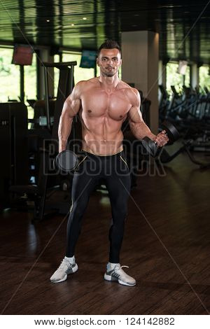 Young Man Doing Exercise For Biceps With Dumbbells