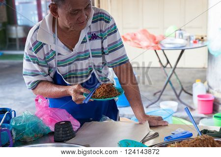 GEORGE TOWN MALAYSIA - MARCH 23 2016: Senior man is selling fried noodles at Kimberly Street Food Night Market on March 23 2016 in George Town Malaysia.