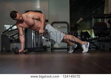 Bodybuilder Doing Push Ups With Dumbbells On Floor