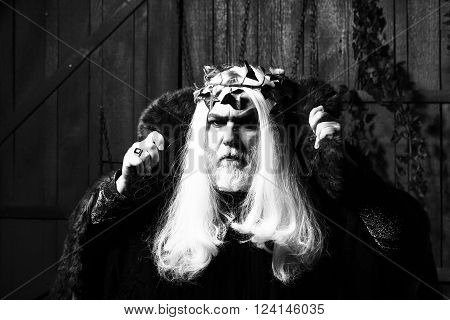 Bearded senior man in long white wig vine crown as Zeus god in fur coat indoor on wooden background