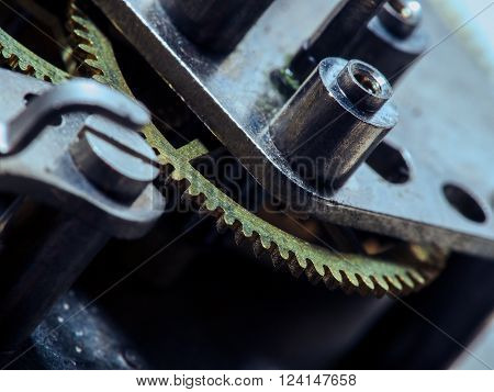 Dismantled clock mechanism. Gears of golden metal can be seen in the complex mechanism. Brass gear lie on the disassembled hours. The complex mechanism of small size. Inside the clock.