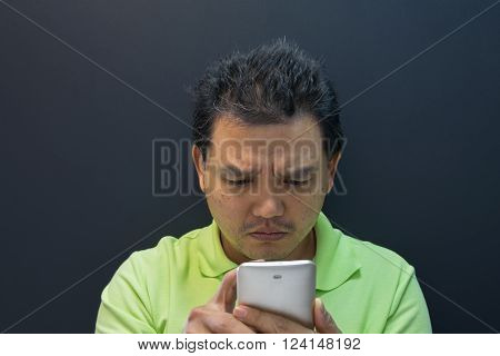 Asia man confused and worried using smartphone on black background