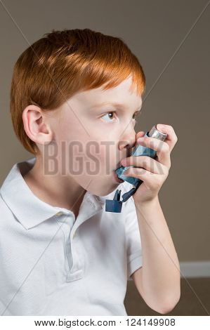Little boy with asthma using his inhaler to help him breathe.