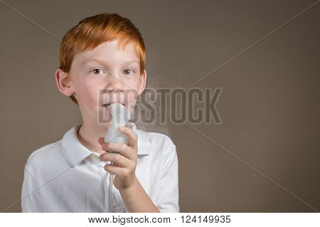 Young boy with respiratory problems completing a breathing treatment with a nebulizer.